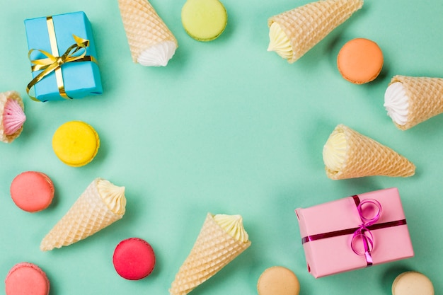 Waffle cones; macaroons and wrapped gift boxes on mint green backdrop