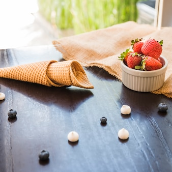 Waffle cones near fresh berries in bowl and napkin on table