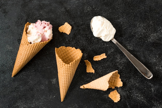Waffle cones near spoon with ice cream