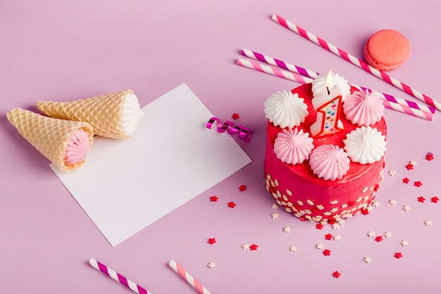 Waffle cones on paper near the delicious cake with sprinkles and drinking straws on purple backdrop