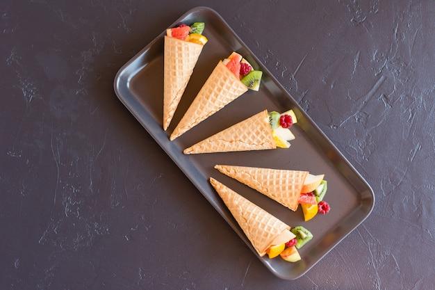 Вафельные рожки со свежими фруктами на черном подносе. вид сверху. вкусный десерт.