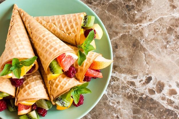 Вафельные рожки со спелыми фруктами на тарелке на мраморном столе