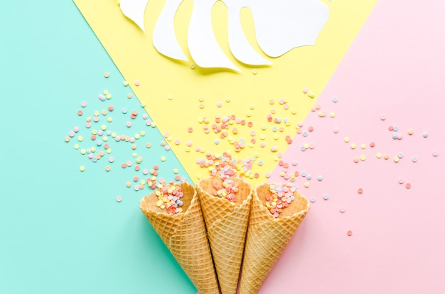 Waffle cones with sugar sprinkles and palm leaf