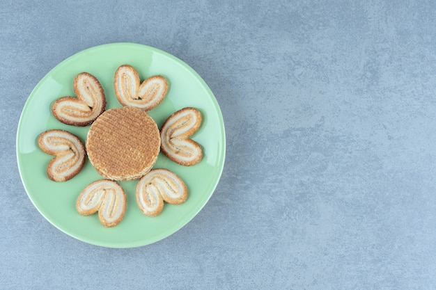 Waffle e biscotti sulla piastra verde su grigio.