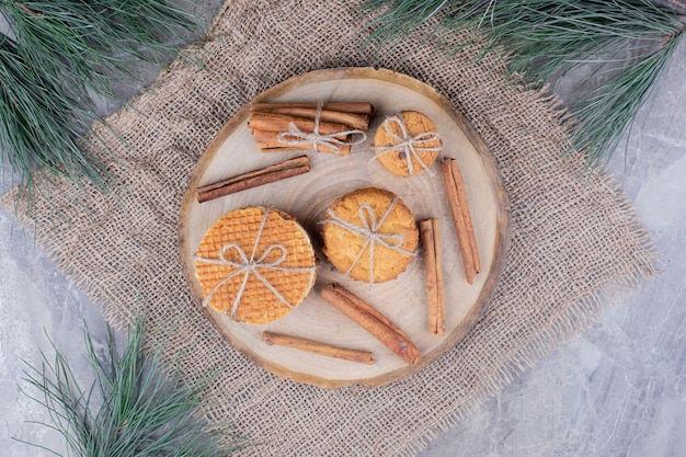 シナモンスティックと木の板にワッフルクッキー