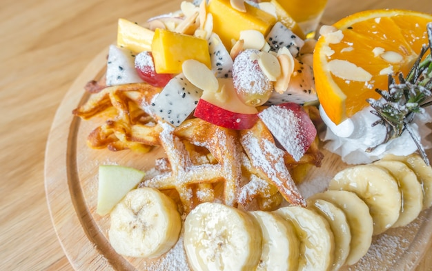 Waffle and fruit with ice cream on table .