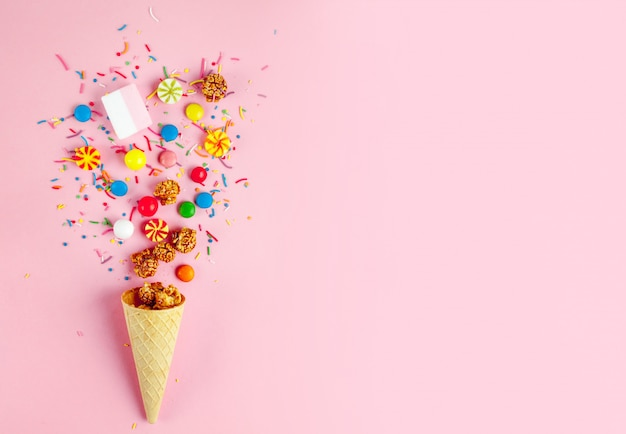 Waffle horn with colored candy, sweets, marshmallow, caramel popcorn, sweet powder on a pink background.