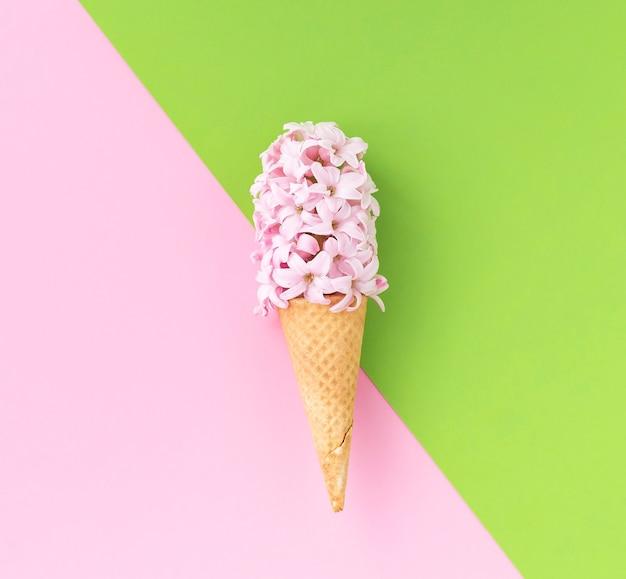 ピンクグリーンの背景にピンクのヒヤシンスの花とワッフルアイスクリームコーン。春のコンセプト。