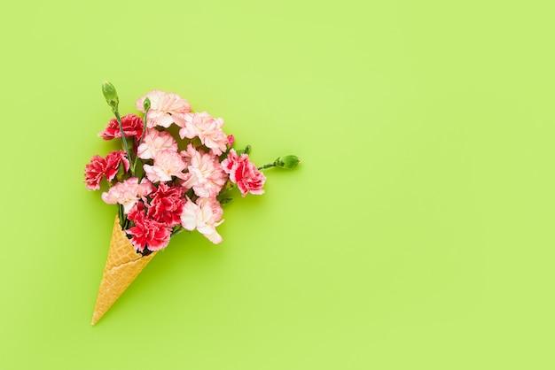 녹색 배경 여름 개념 복사에 빨간색과 분홍색 카네이션 꽃과 와플 아이스크림 콘