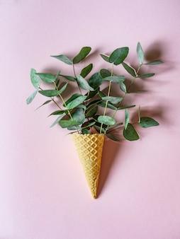 Waffle ice cream cone with twigs of green eucalyptus