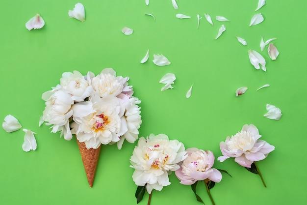 緑の背景に白い牡丹の花とワッフルアイスクリームコーン。夏のコンセプト。コピースペース、上面図。ミニマリズム