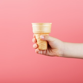 ピンクの背景に子供の手でワッフルアイスクリームカップ。
