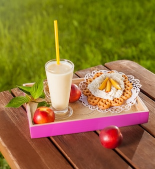 Waffle and milkshake on wooden table in the garden