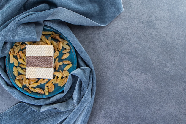 Waffle and raisins on a wooden plate on the piece of fabric on the marble surface