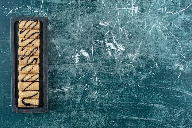 Вафельный рулет на доске, на синем фоне. фото высокого качества