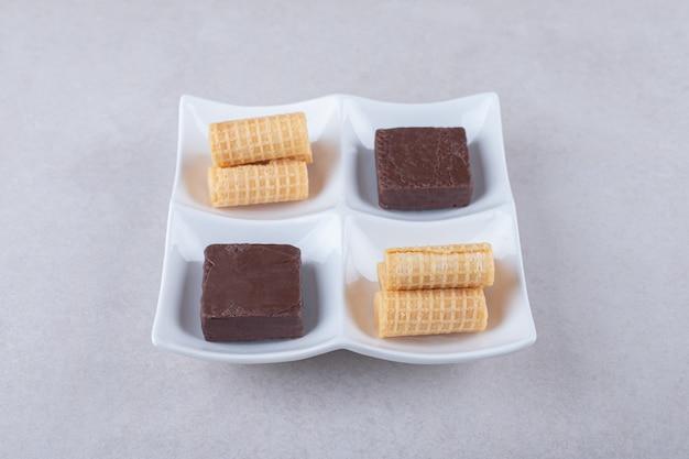 大理石のテーブルの上の皿にワッフルロールとチョコレートでコーティングされたウエハース。