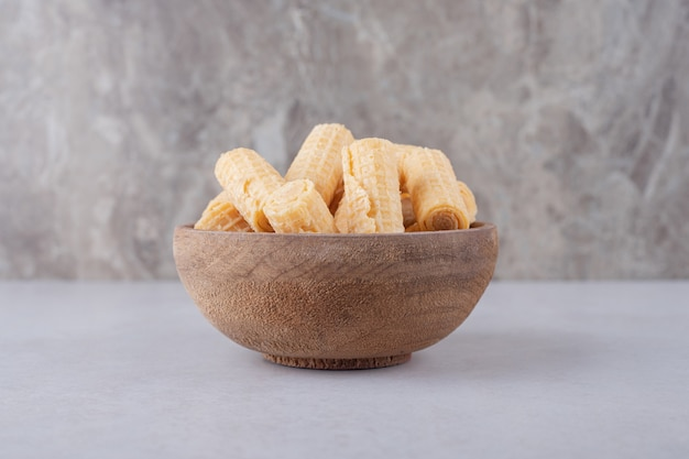 Waffle rolls in a bowl on marble table.