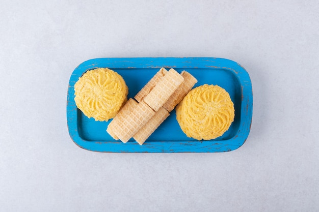 Rotoli di cialda e biscotti sul piatto di legno, il marmo.