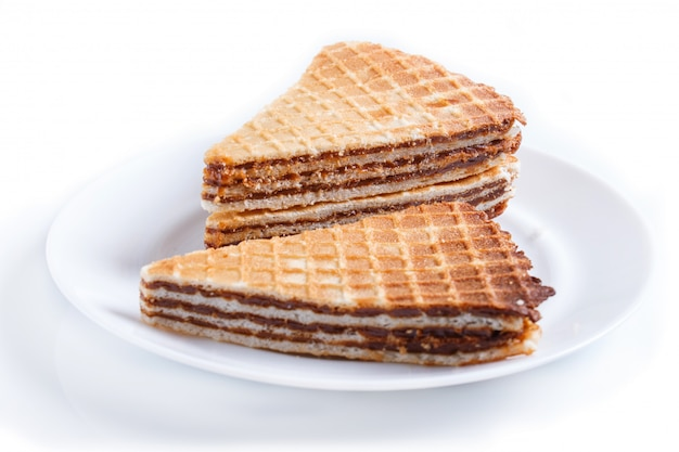 Waffle sandwiches with boiled condensed milk in plate isolated on white background.