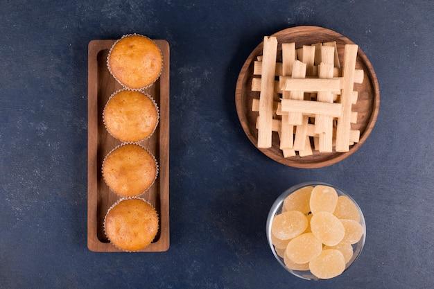 マーマレードとカップケーキを脇に置いた木製の大皿に山積みされたワッフルスティック