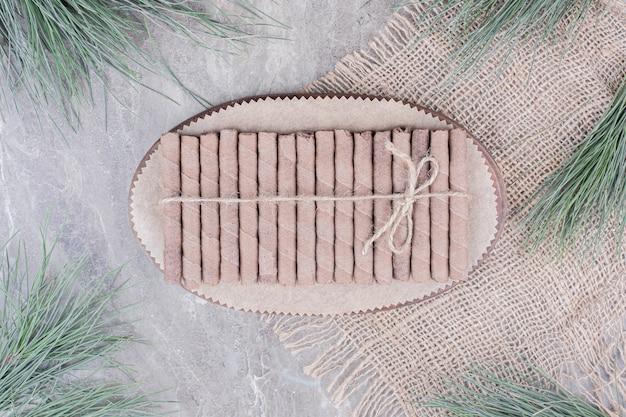 Bastoncini di cialda avvolti con un filo su una tavola di legno