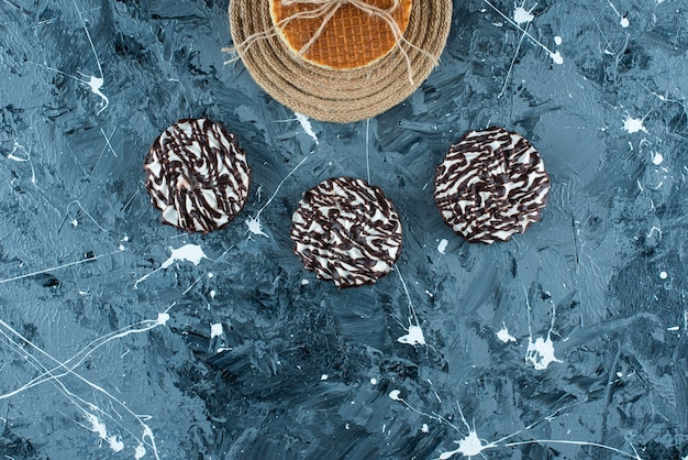 Waffle su un sottopentola accanto al biscotto al cioccolato, sul tavolo blu.