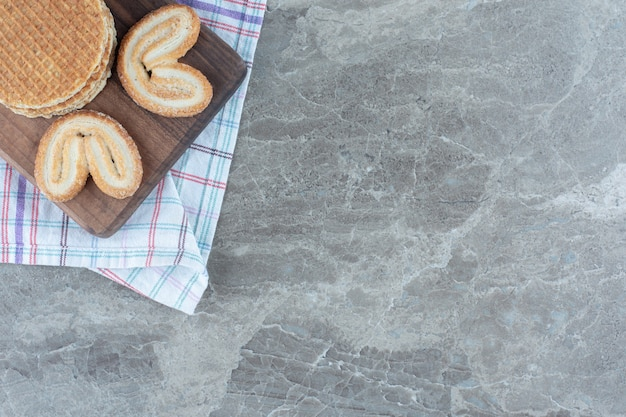 灰色の背景の上に木の板にクッキーとワッフル。
