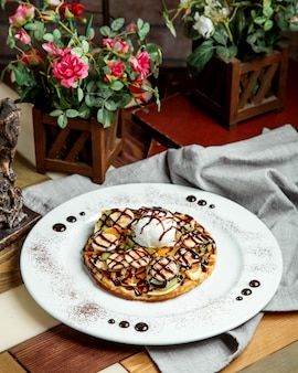 Waffle with fruits banana kiwifruit vanilla ice cream and chocolate sauce
