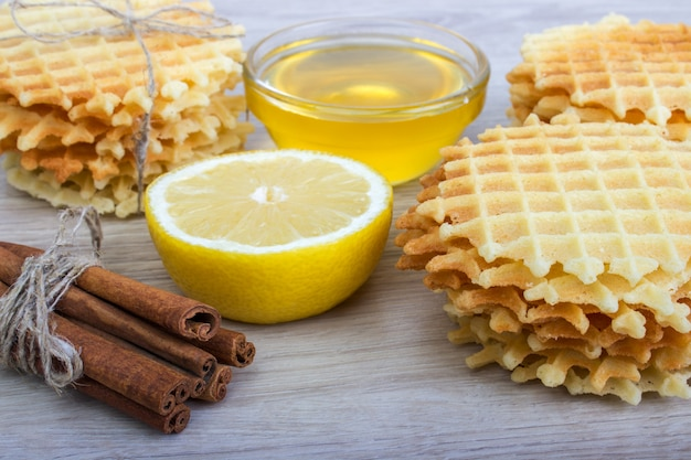 Waffle with honey,cinnamon, lemon on a light wooden background