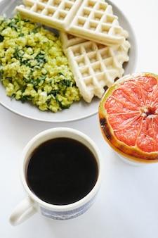 Вафли с ломтиками грейпфрута на белой керамической тарелке