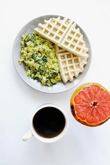 Waffle con pompelmo a fette sul piatto in ceramica bianca