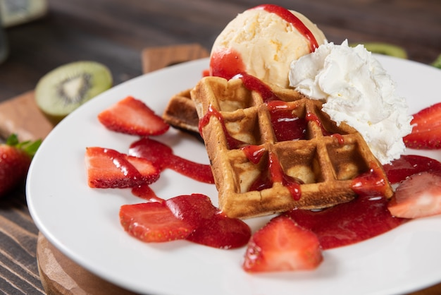 Waffle with strawberries, vanilla ice cream and whipped cream