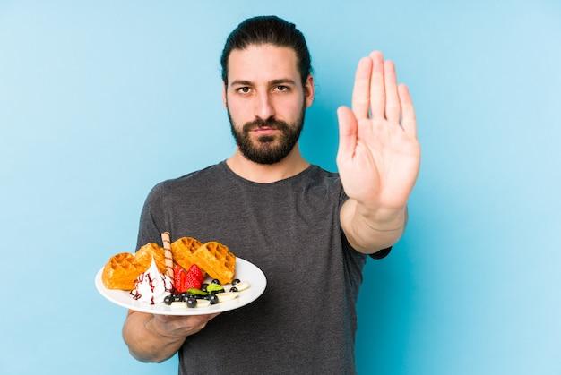 Молодой кавказский человек есть десерт waffle изолировал положение при протягиванный знак стопа показа руки, предотвращая вас.