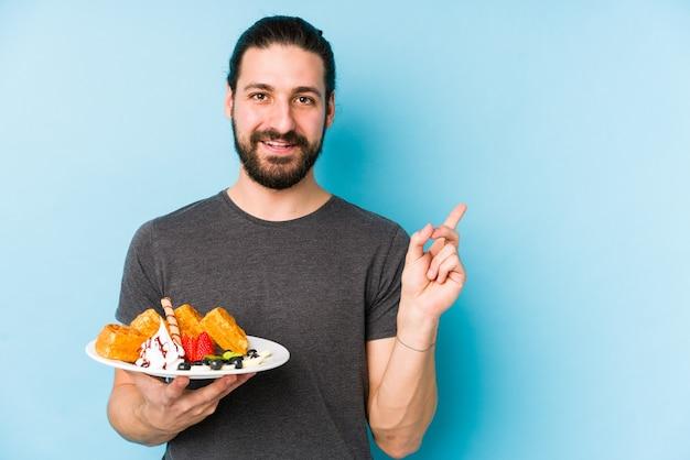 Молодой кавказский человек есть десерт waffle изолировал усмехаться и указывать в сторону, показывая что-то на пустом пространстве.