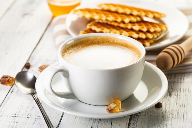 白い木製のテーブルにワッフルとコーヒー