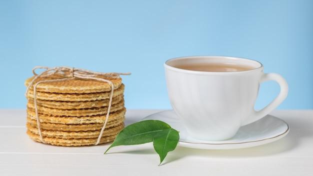 파란색 배경에 흰색 테이블에 녹색 잎이 있는 와플과 차. 차와 함께 만든 수제 케이크.