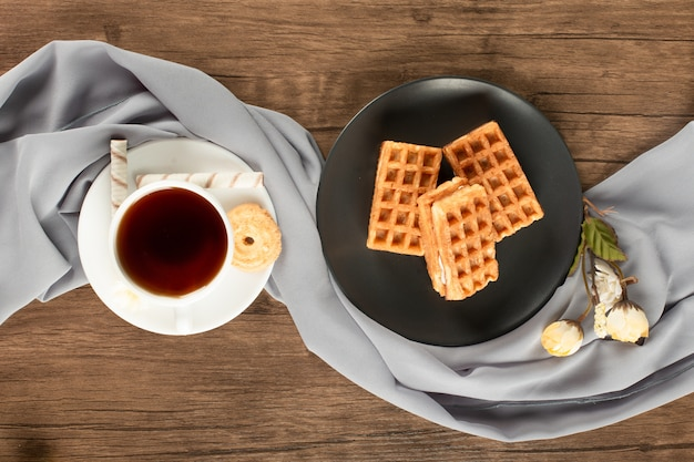 Waffles on a black saucer, a cup of tea on the wood table.top view