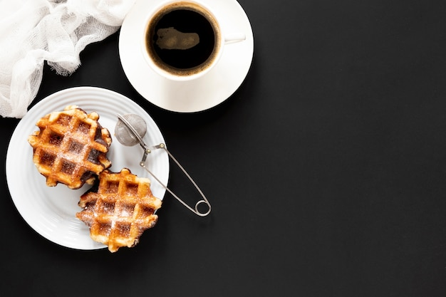 Waffles and coffee on black table