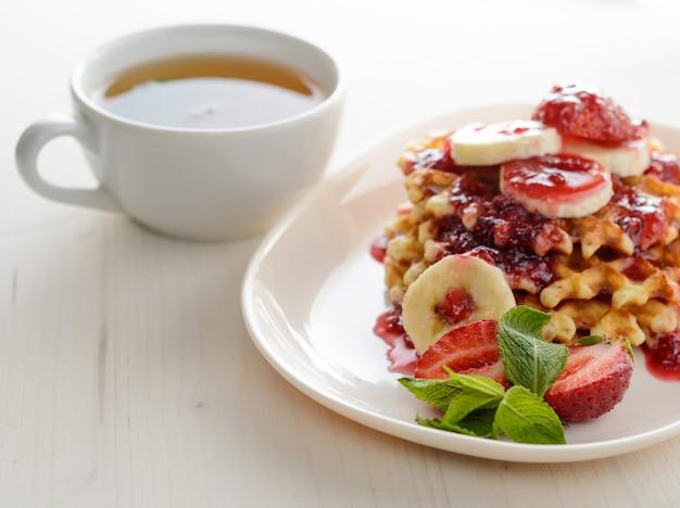 いちごバナナとミントのワッフルデザート。健康的な朝食のためのティーカップ