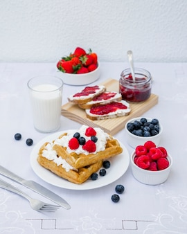 Waffles, milk and berry fruits on table
