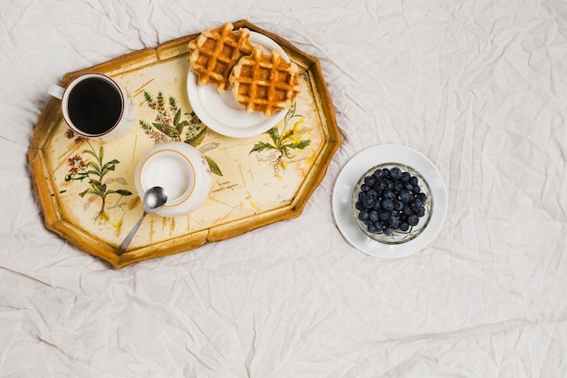 Waffles; milk jar; coffee cup and blueberries bowl on white crumpled tablecloth