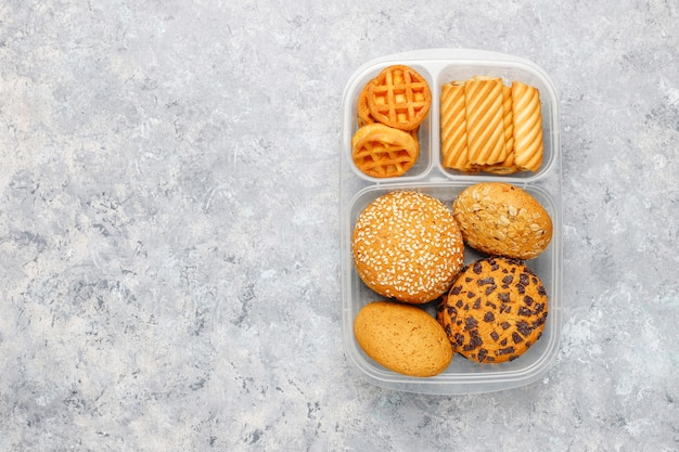 クッキー、waffles.muffins、コンクリート表面の不健康なランチボックス