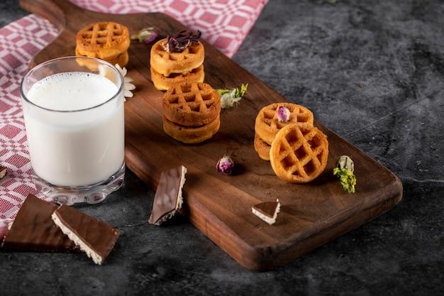 Вафли на деревянной доске с чашкой молока.