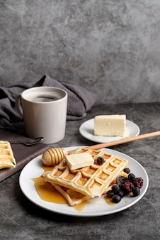 Waffles on plate with honey and butter