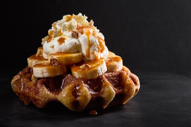 Waffles with bananas topped with caramel syrup on a dark stone background