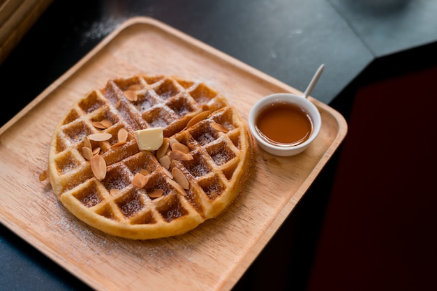 Waffles with butter on wooden plate