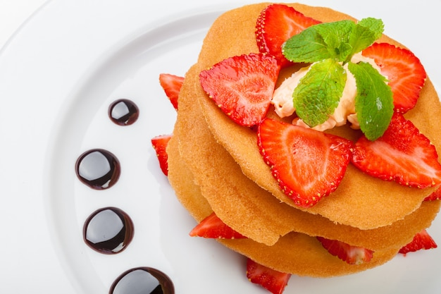 Waffles with caramel sauce, whipped cream and strawberries isolated on white