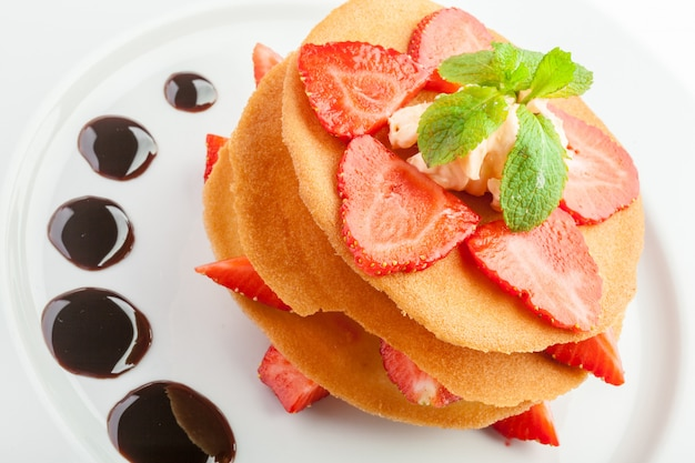 Waffles with caramel sauce, whipped cream and strawberries isolated