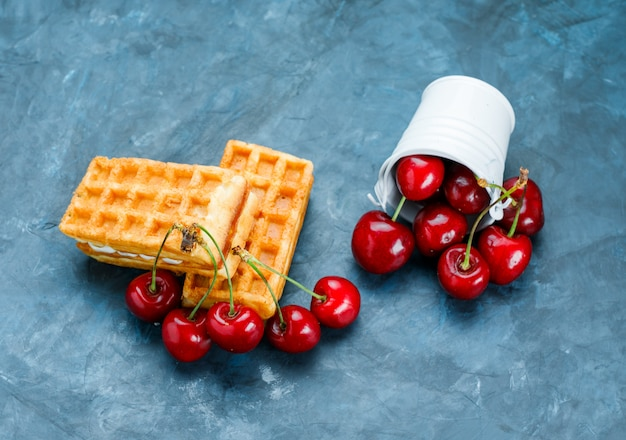 Waffles with cherries on grungy blue surface, flat lay.