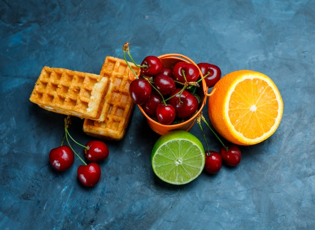 Waffles with cherries, orange, lime on grungy blue surface, flat lay.